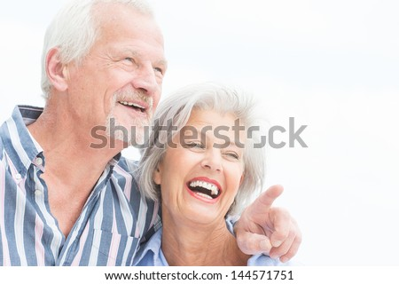 Portrait from a happy senior couple in front of cloudy sky - stock photo