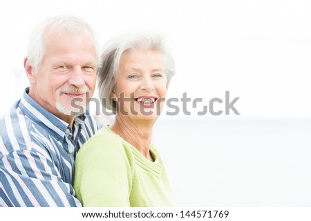 Portrait from a happy senior couple in front of cloudy sky