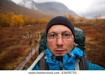 Portrait from a long distance hiker in Lapland on a rainy day in autumn - stock photo