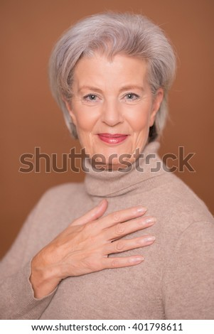 Portrait from a senior woman in front of brown background - stock photo