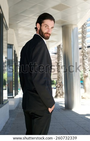 Portrait from behind of a male fashion model in black business suit standing outdoors