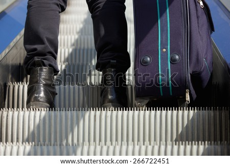 Portrait from behind of a man standing on escalator with travel bag - stock photo