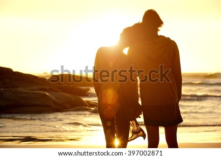 Portrait from behind of loving couple holding hands at the beach and watching the sunset - stock photo