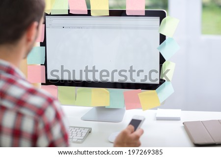 Portrait from behind of young man  using computer with notes on it,  a lot of things to do - stock photo