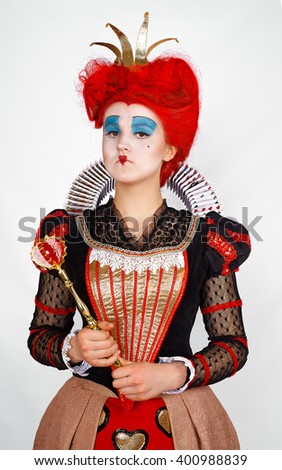 Portrait girl in costume Red Queen with crown and scepter