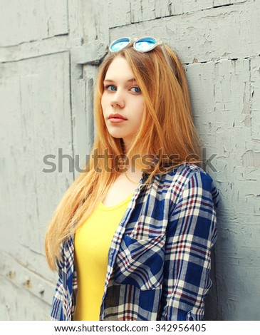 Portrait girl wearing checkered shirt and sunglasses in city - stock photo