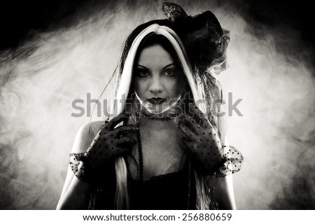 Portrait gothic girl in style clothes, shot over smoky background - stock photo