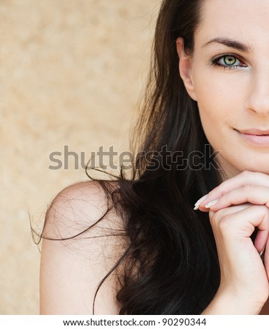 portrait half of face lovely woman smiling dark-haired bare shoulders - stock photo