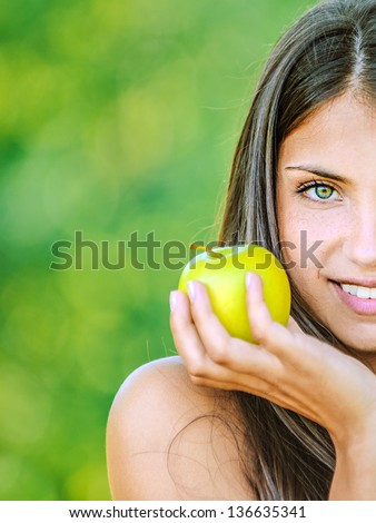 Portrait half of face young beautiful woman with bare shoulders holding an apple and smiling, on green background summer nature. - stock photo