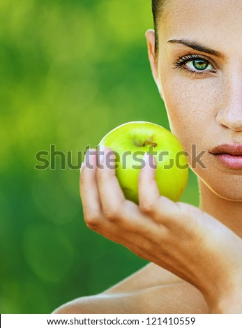Portrait half of face young beautiful woman with bare shoulders holding an apple, on green background summer nature. - stock photo