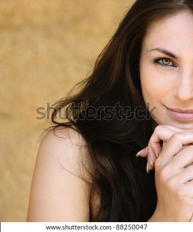 Portrait half of young alluring smiling attractive brunnete woman propping up her face against yellow background. - stock photo