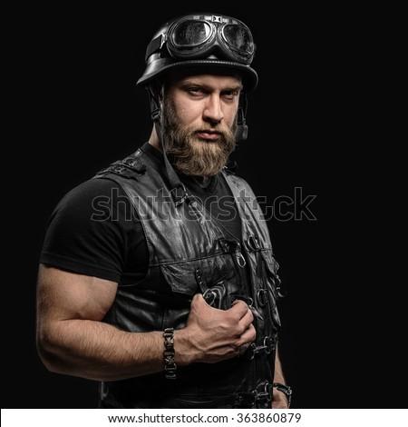Portrait Handsome Bearded Biker Man in Leather Jacket and Helmet over Black Background - stock photo