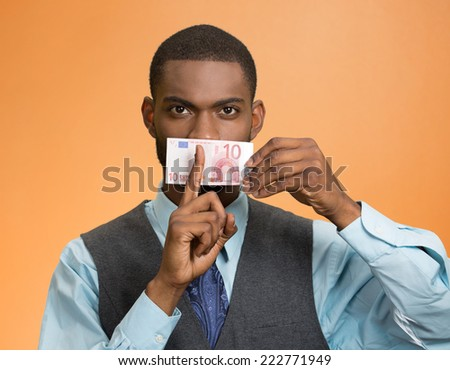 Portrait handsome corrupt guy businessman holding euro bill to mouth showing shhh sign finger to lips isolated on orange background. Bribery concept in politics, business diplomacy. Face expression - stock photo