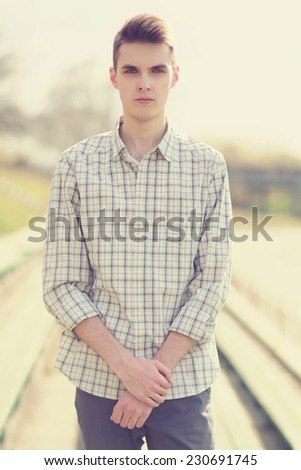 Portrait handsome hipster man in smart casual clothes with stylish hairstyle outdoors - stock photo