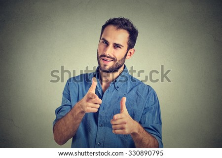 Portrait handsome young smiling man giving thumbs up pointing fingers at camera, picking you as friend isolated on grey wall background. Positive human emotion facial expression sign body language - stock photo