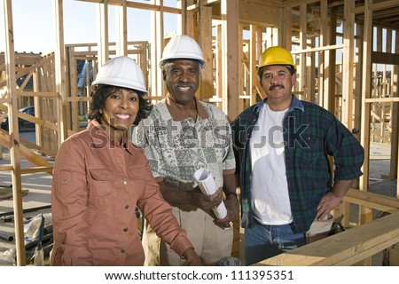 Portrait happy african american couple with architect at construction site - stock photo
