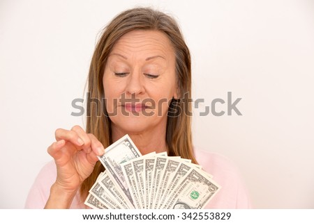 Portrait happy attractive mature woman holding US dollar notes, isolated, bright background. - stock photo