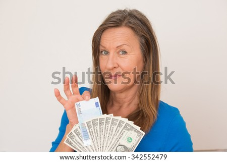 Portrait happy attractive mature woman presenting Euro and US dollar money, isolated, bright background. - stock photo