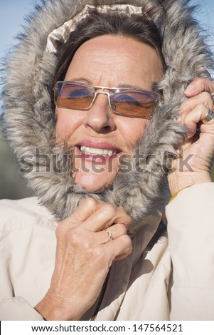 Portrait happy attractive mature woman wearing warm winter jacket with hood and sunglasses, joyful smiling with blurred background.
