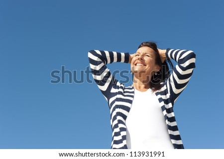 Portrait Happy attractive senior woman with relaxed expression, isolated with blue sky as background and copy space. - stock photo