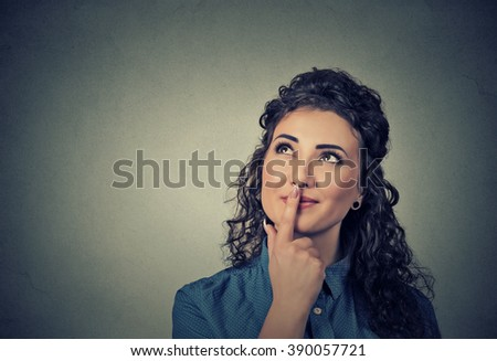 Portrait happy beautiful woman thinking looking up isolated on gray wall background with copy space. Human face expressions, emotions, feelings, body language, perception  - stock photo
