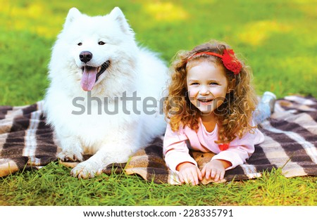 Portrait happy child and dog having fun outdoors  - stock photo