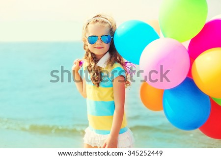 Portrait happy child on summer beach with colorful balloons over sea - stock photo