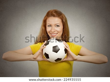 Portrait happy football girl in yellow t-shirt on grey wall background. Positive face expression, emotion, feeling. healthy life style concept - stock photo