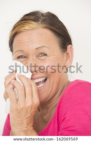 Portrait happy friendly mature woman sneezing, cleaning nose with tissue, smiling, laughing, isolated on white. - stock photo