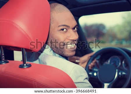 Portrait happy handsome young man in new car hands on wheel, turning around, smiling looking at, talking to passengers sitting in back seat. Driver license exam, test concept  - stock photo