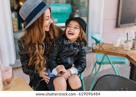 Portrait happy loving family, mother and daughter sitting in city cafe playing and hugging. Mother and daughter laugh sincerely. Styling family, true emotions, good day.
