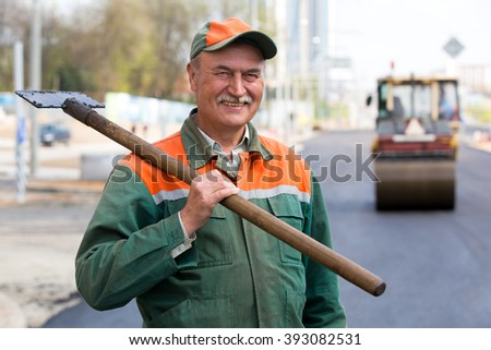 Portrait happy male road construction worker with asphalt pavement scraper tool during blacktopping tarmacadam surface works - stock photo