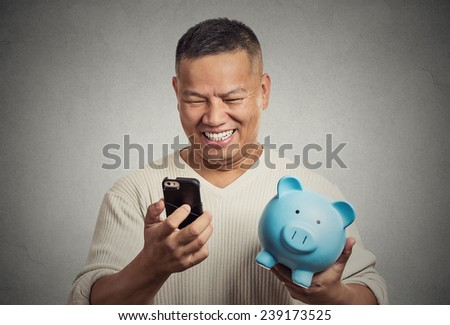 Portrait happy man employee holding piggy bank looking at smart phone isolated grey background. Financial savings banking concept, customer satisfaction contract agreement. Positive face expression - stock photo