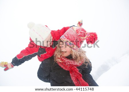 Portrait happy mother and child together in snow  laughing, smiling - stock photo