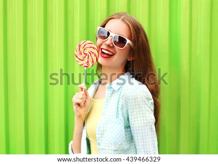 Portrait happy pretty smiling woman with lollipop over colorful green background - stock photo