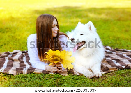 Portrait happy pretty woman and white Samoyed dog on the plaid outdoors  - stock photo