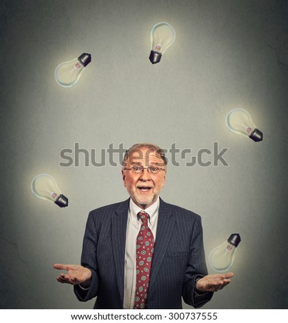 Portrait happy senior business man executive in suit juggling playing with light bulbs isolated on gray office wall background  - stock photo