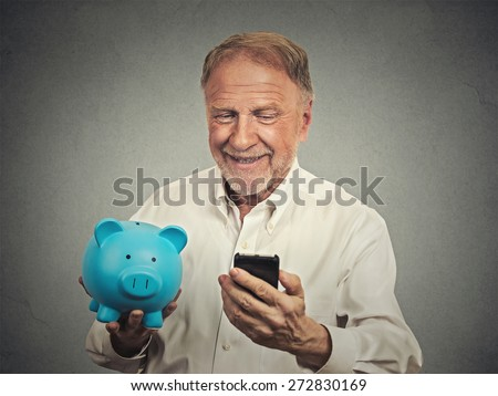 Portrait happy senior man holding piggy bank looking at smart phone isolated grey background. Financial savings banking concept, customer satisfaction contract agreement. Positive face expression  - stock photo