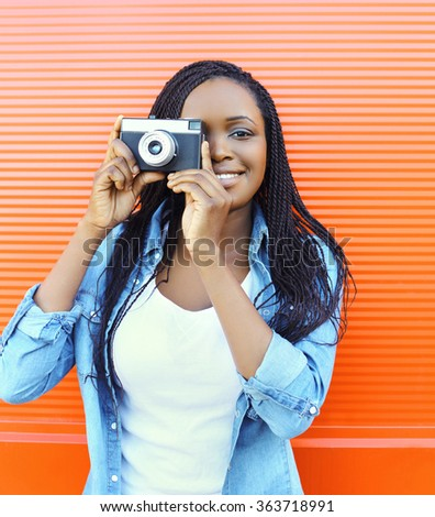 Portrait happy smiling african woman with old vintage camera over red background - stock photo