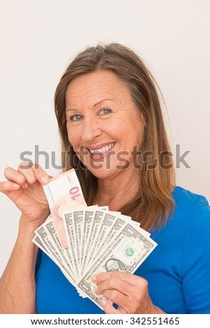 Portrait happy smiling attractive mature woman presenting Euro and US dollar currency, isolated, bright background.