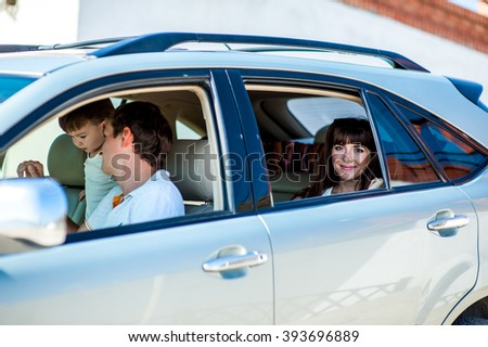 Portrait happy, smiling Family, mother, father, one kid sitting in the white, silver car looking out windows, ready for vacation trip. Positive Human face expression, emotions, feelings