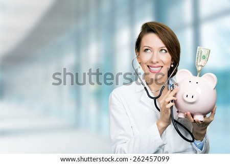 Portrait happy smiling female doctor holding listening to piggy bank with stethoscope standing in hospital hallway on clinic office windows background  - stock photo