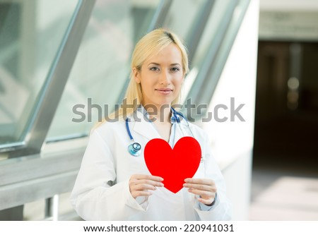 Portrait happy smiling female health care professional, woman family doctor cardiologist with stethoscope holding red heart isolated hospital hallway background. Patient plan. Positive face expression - stock photo