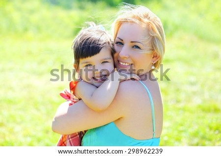 Portrait happy smiling mother and child having fun together outdoors in summer sunny day - stock photo