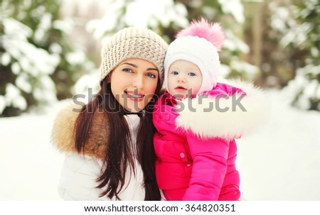 Portrait happy smiling mother and child in snowy winter day