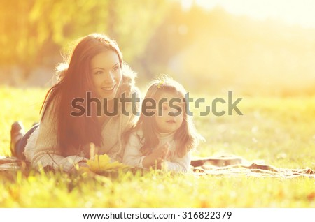 Portrait happy smiling mother and child together in autumn park - stock photo