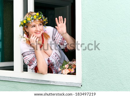 Portrait Happy Ukrainian woman in the window - stock photo
