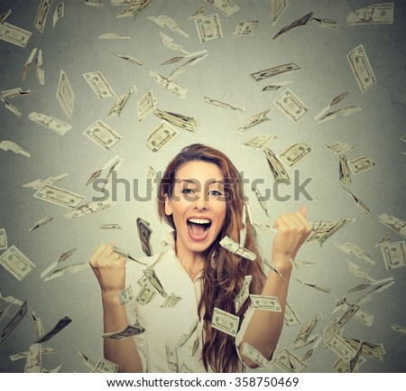 Portrait happy woman exults pumping fists ecstatic celebrates success under a money rain falling down dollar bills banknotes isolated on gray wall background with copy space   - stock photo