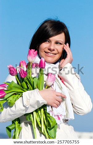 Portrait happy women with pink tulips talking by a cellular telephone - stock photo