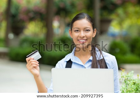 Portrait happy young business woman holding credit card and laptop making online oder, shopping concept isolated outdoors, outside background. Positive facial expressions, emotions. Smiling customer - stock photo